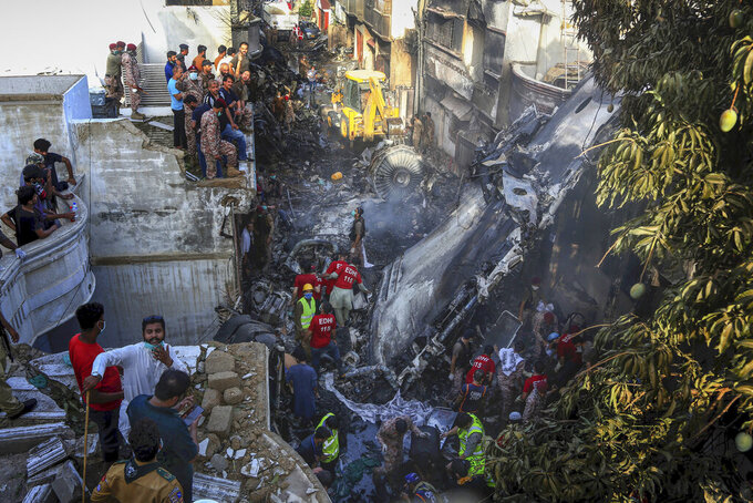 Volunteers look for survivors of a plane that crashed in a residential area of Karachi, Pakistan, May 22, 2020. An aviation official says a passenger plane belonging to state-run Pakistan International Airlines carrying more than 100 passengers and crew has crashed near the southern port city of Karachi. (AP Photo/Fareed Khan)