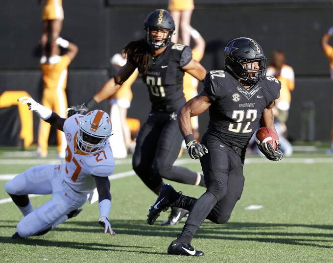 Vanderbilt running back Jamauri Wakefield (32) carries the ball past Tennessee defensive back Carlin Fils-aime (27) in the first half of an NCAA college football game Saturday, Nov. 24, 2018, in Nashville, Tenn. (AP Photo/Mark Humphrey)
