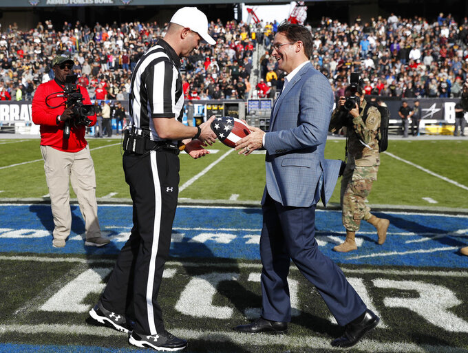 Secretary of the United States Army Mark Esper, right, presents the game ball to referee Luke Richmond during the opening ceremonies of the Armed Forces Bowl NCAA college football game between Houston and Army, Saturday, Dec. 22, 2018, in Fort Worth, Texas. (AP Photo/Jim Cowsert)