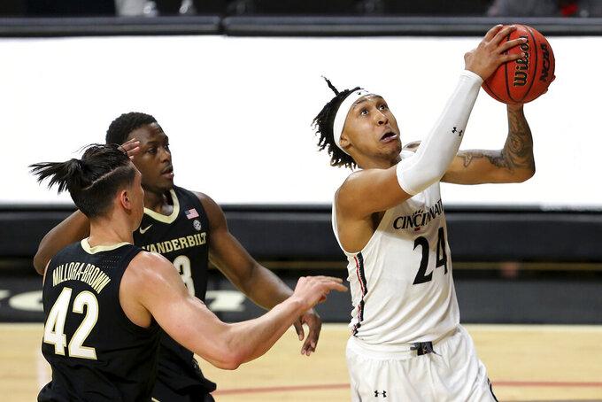 Cincinnati guard Jeremiah Davenport (24) shoots as Vanderbilt guard Maxwell Evans (3) defends during the first half of an NCAA college basketball game Thursday, March 4, 2021, in Cincinnati. (Kareem Elgazzar/The Cincinnati Enquirer via AP)