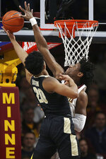 Minnesota's center Daniel Oturu, right, blocks the shot of Purdue's Nojel Eastern, left, during the first half of an NCAA basketball game Tuesday, March 5, 2019, in Minneapolis. (AP Photo/Stacy Bengs)