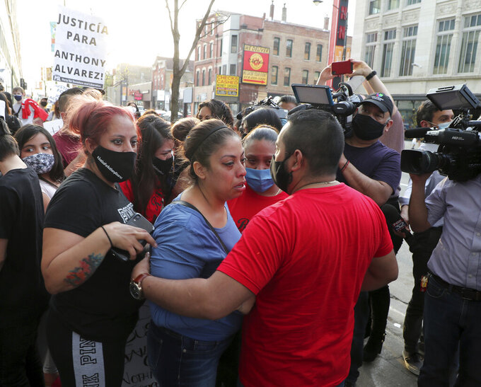 Veronica Alvarez, center,  the mother of 22-year-old Anthony Alvarez, is comforted by supporters on Tuesday, April 27, 2021, outside the headquarters of the Civilian Office of Police Accountability in Chicago.  Chicago's independent police review board has released video of the 22-year-old Latino man who was shot in the back late last month during a foot chase.   (Jose M. Osorio /Chicago Tribune via AP)