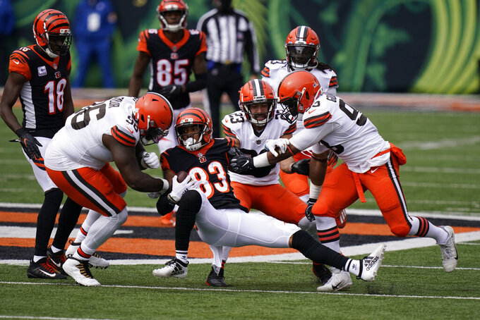 Cincinnati Bengals' Tyler Boyd (83) is tackled by Cleveland Browns' Vincent Taylor (96), Andrew Sendejo (23) and B.J. Goodson (93) during the first half of an NFL football game, Sunday, Oct. 25, 2020, in Cincinnati. (AP Photo/Bryan Woolston)