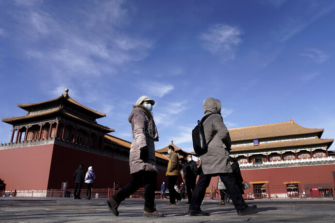 Visitors wearing face masks to help curb the spread of the coronavirus walk by Forbidden City in Beijing, Sunday, Jan. 10, 2021. More than 360 people have tested positive in a growing COVID-19 outbreak south of Beijing in neighboring Hebei province. (AP Photo/Andy Wong)