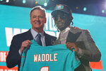 Alabama wide receiver Jaylen Waddle, right, holds a team jersey with NFL Commissioner Roger Goodell after being chosen by the Miami Dolphins with the sixth pick in the NFL football draft Thursday April 29, 2021, in Cleveland. (AP Photo/Tony Dejak)