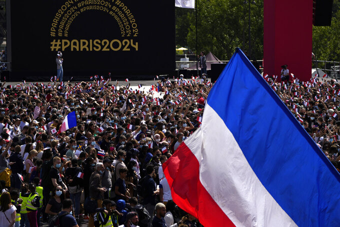 A fan waves the French flag in the Olympics fan zone at Trocadero Gardens in front of the Eiffel Tower in Paris, Sunday, Aug. 8, 2021. A celebration was held in Paris Sunday as part of the handover ceremony of Tokyo 2020 to Paris 2024, as Paris will be the next Summer Games host in 2024. The passing of the hosting baton will be split between the Olympic Stadium in Tokyo and a public party and concert in Paris. (AP Photo/Francois Mori)