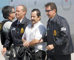 FILE - In this May 13, 2008 file photo, Colombian paramilitary Hernan Giraldo Serna, second right, is escorted by U.S. DEA Agents at his arrival in Opa-locka, Fla. Giraldo Serna has been deported from the US and returned to Colombian on Monday, January 25, 2021, after finishing a 16-year sentence in a U.S. prison for drug trafficking earlier this month. (AP Photo/Alan Diaz, File)