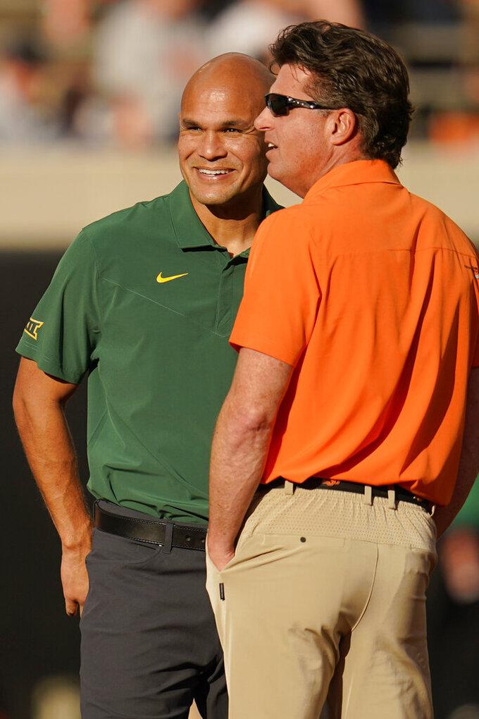 Baylor head coach Dave Aranda, left, and Oklahoma State head coach Mike Gundy talk before their NCAA college football game, Saturday, Oct. 2, 2021, in Stillwater, Okla. (AP Photo/Sue Ogrocki)