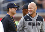 Michigan head coach Jim Harbaugh, left, talks with Maryland interim head coach Matt Canada during warmups before an NCAA football game in Ann Arbor, Mich., Saturday, Oct. 6, 2018. (AP Photo/Paul Sancya)