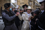 Ultra-Orthodox Jews, some wearing costumes, scuffle with police officers during celebrations of the Jewish holiday of Purim, in the Mea Shearim neighborhood of Jerusalem, Sunday, Feb. 28, 2021. Purim commemorates the Jews' salvation from genocide in ancient Persia, as recounted in the biblical Book of Esther. (AP Photo/Oded Balilty)