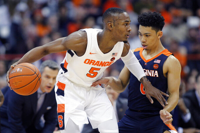 Syracuse's Jalen Carey, left, dribbles past Virginia's Kihei Clark, right, during the first half of an NCAA college basketball game in Syracuse, N.Y., Wednesday, Nov. 6, 2019. (AP Photo/Nick Lisi)