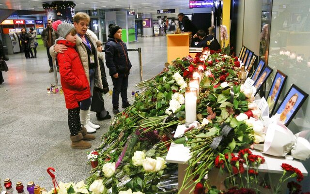People look at a memorial at Borispil international airport outside in Kyiv, Ukraine, Thursday, Jan. 9, 2020, for the flight crew members of the Ukrainian 737-800 plane that crashed on the outskirts of Tehran. The crew of a Ukrainian jetliner that crashed in Iran, killing all 176 people on board, never made a radio call for help and was trying to turn back for the airport when the burning plane went down, an initial Iranian investigative report said Thursday. (AP Photo/Efrem Lukatsky)