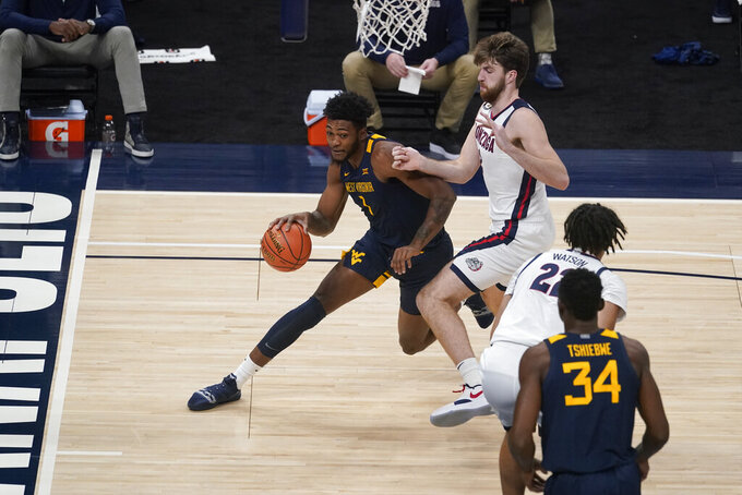 West Virginia's Gabe Osabuohien (3) goes to the basket against Gonzaga's Drew Timme during the first half of an NCAA college basketball game Wednesday, Dec. 2, 2020, in Indianapolis. (AP Photo/Darron Cummings)