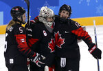 Lauriane Rougeau (5), goalie Shannon Szabados (1) and Meaghan Mikkelson (12), of Canada, celebrate after the preliminary round of the women's hockey game against Finland at the 2018 Winter Olympics in Gangneung, South Korea, Tuesday, Feb. 13, 2018. Canada won 4-1. (AP Photo/Frank Franklin II)