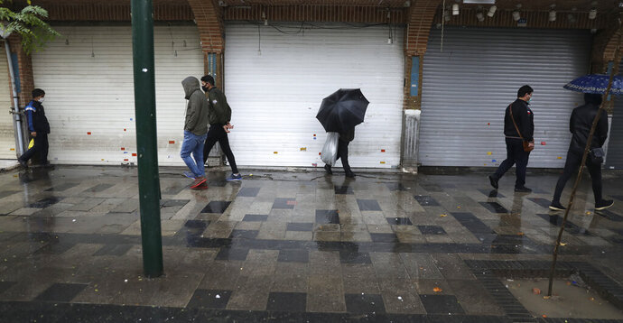 People walk in front of closed shops at Tehran's Grand Bazaar, Iran's main business and trade hub, Satuday, Nov. 21, 2020. Iran on Saturday shuttered businesses and curtailed travel between its major cities, including the capital of Tehran, as it grapples with the worst outbreak of the coronavirus in the Mideast region. (AP Photo/Vahid Salemi)