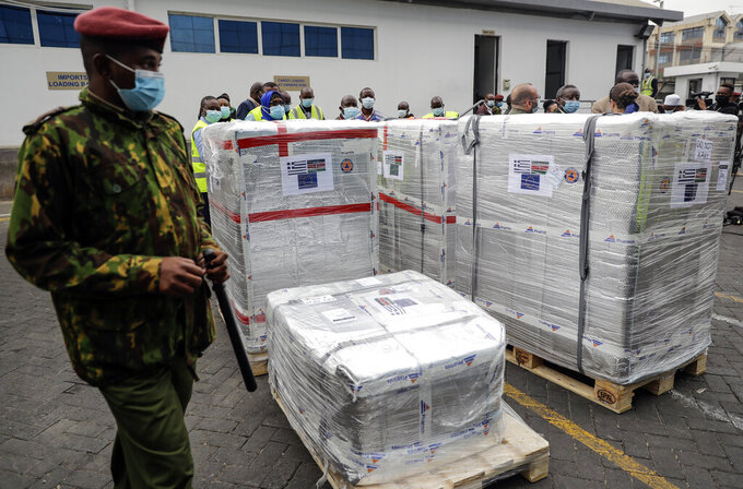 FILE - In this file Friday, Aug.6. 2021 file photo, a Kenyan soldier guards a consignment of 182,000 AstraZeneca vaccines from the Greek Government via the COVAX facility, at Kenya Jomo Kenyatta airport in Nairobi. In late June, the international system for sharing coronavirus vaccines sent about 530,000 doses to Britain – more than double the amount sent that month to the entire continent of Africa. It was the latest example of how a system that was supposed to guarantee low and middle-income countries vaccines is failing, leaving them at the mercy of haphazard donations from rich countries.(AP Photo/Brian Inganga, file)