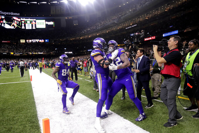 Minnesota Vikings tight end Kyle Rudolph, right, is greeted by teammates after catching the game winning touchdown pass during overtime of an NFL wild-card playoff football game against the New Orleans Saints, Sunday, Jan. 5, 2020, in New Orleans. The Vikings won 26-20. (AP Photo/Brett Duke)