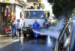 In this photo released by the Syrian official news agency, SANA, a Syrian worker disinfectants a street to prevent the spread of the coronavirus, in Damascus, Syria, Monday, Aug. 3, 2020. At least four of Syria's national soccer team players and three technical team members have tested positive for coronavirus and are in isolation, a Syrian official said Tuesday. (SANA via AP)