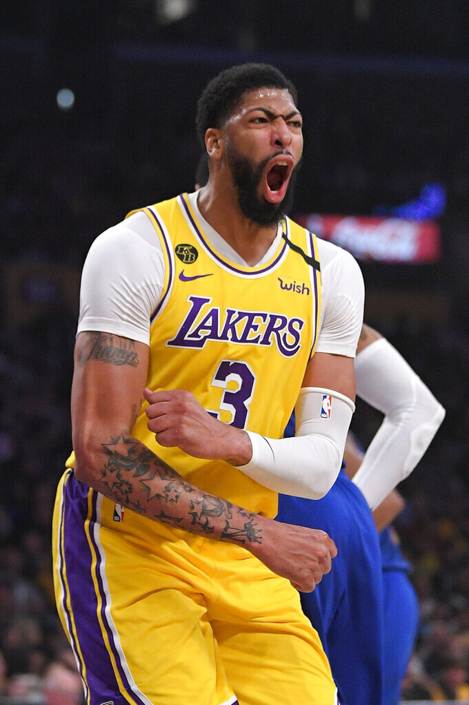 FILE - In this March 3, 2020, file photo, Los Angeles Lakers forward Anthony Davis celebrates after scoring during the first half of an NBA basketball game against the Philadelphia 76ers, in Los Angeles. Jusuf Nurkic is back and healthy. So are Zach Collins, Meyers Leonard, Giannis Antetokounmpo, Anthony Davis and plenty of others. If the four-month NBA shutdown had a silver lining, it's that a lot of ailing players got well.(AP Photo/Mark J. Terrill, File)