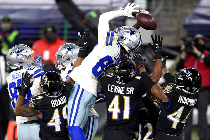 Dallas Cowboys wide receiver CeeDee Lamb, center, is unable to catch a Hail Mary pass from quarterback Andy Dalton as a host of Baltimore Ravens defenders compete for the ball during the first half of an NFL football game, Tuesday, Dec. 8, 2020, in Baltimore. (AP Photo/Nick Wass)