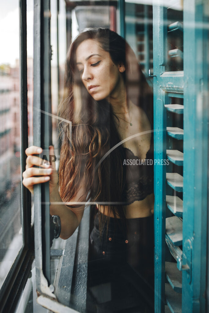 Lonely woman holding glass window