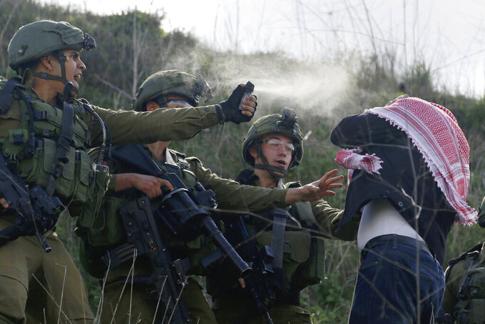 Israeli soldiers use pepper spray on a Palestinian demonstrator near the Jewish settlement Yitzhar, near the West Bank city of Nablus, on Friday, Feb. 21, 2020. Israeli Prime Minister Benjamin Netanyahu announced Thursday he was pushing ahead with the construction of 5,000 new Jewish homes in key areas of east Jerusalem, where critics say additional building could cut Palestinian residents off from the rest of the West Bank. (AP Photo/Majdi Mohammed).