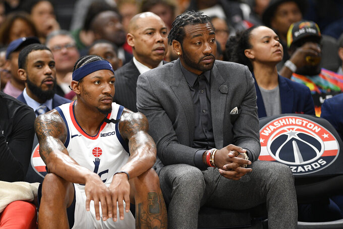 Washington Wizards guard Bradley Beal, left, and guard John Wall, right, watch from the bench during the second half of an NBA basketball game against the Milwaukee Bucks, Monday, Feb. 24, 2020, in Washington. The Wizards won't have Beal, Wall or Davis Bertans when the NBA returns amid the coronavirus pandemic. When the league stopped play in March because of the COVID-19 outbreak, the Wizards were 24-40 and ninth in the Eastern Conference. (AP Photo/Nick Wass, File)