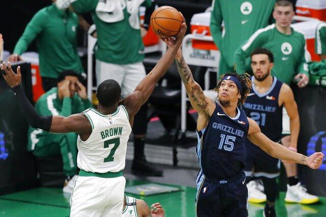 Boston Celtics' Jaylen Brown (7) and Memphis Grizzlies' Brandon Clarke (15) battle for a rebound during the first half of an NBA basketball game, Wednesday, Dec. 30, 2020, in Boston. (AP Photo/Michael Dwyer)