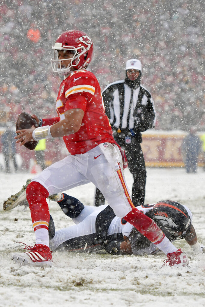 Kansas City Chiefs quarterback Patrick Mahomes avoids a tackle by Denver Broncos defensive lineman Mike Purcell, rear, during the second half of an NFL football game in Kansas City, Mo., Sunday, Dec. 15, 2019. (AP Photo/Ed Zurga)