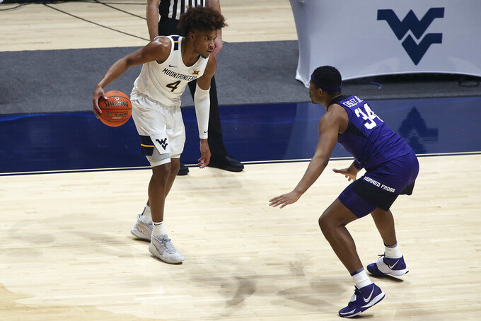 West Virginia guard Miles McBride (4) is defended by TCU forward Kevin Easley (34) during the second half of an NCAA college basketball game Thursday, March 4, 2021, in Morgantown, W.Va. (AP Photo/Kathleen Batten)