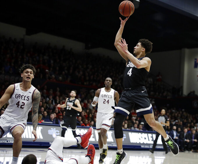 Gonzaga's Ryan Woolridge, right, shoots over St. Mary's Dan Fotu (42) and a fallen player the first half of an NCAA college basketball game Saturday, Feb. 8, 2020, in Moraga, Calif. (AP Photo/Ben Margot)