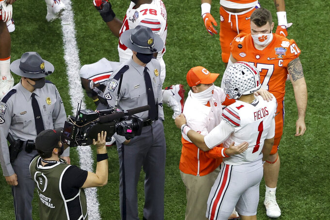 Clemson head coach Dabo Swinney greets Ohio State quarterback Justin Fields on the field after the Sugar Bowl NCAA college football game Friday, Jan. 1, 2021, in New Orleans. Ohio State won 49-28. (AP Photo/Butch Dill)