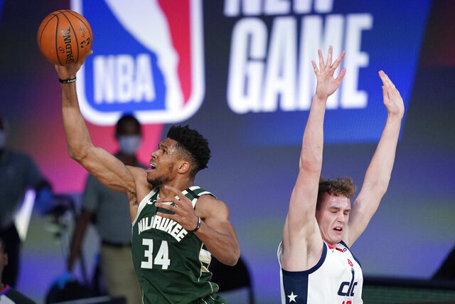 FILE - In this Aug. 11, 2020, file photo, Milwaukee Bucks' Giannis Antetokounmpo (34) drives to the basket past Washington Wizards' Anzejs Pasecniks, right, during the first half of an NBA basketball game, in Lake Buena Vista, Fla. The Orlando Magic and Milwaukee Bucks open the Eastern Conference playoffs Tuesday, Aug. 18, 2020, at Disney's Wide World of Sports. (AP Photo/Ashley Landis, Pool, File)