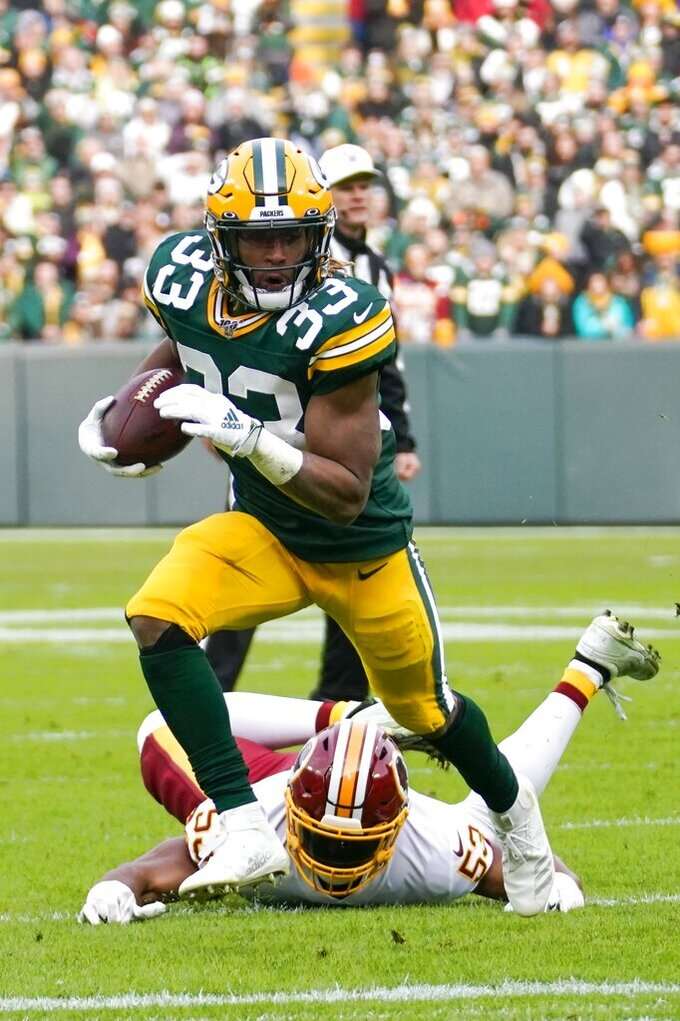 Green Bay Packers' Aaron Jones runs past Washington Redskins' Jon Bostic during the first half of an NFL football game against the Washington Redskins Sunday, Dec. 8, 2019, in Green Bay, Wis. (AP Photo/Morry Gash)