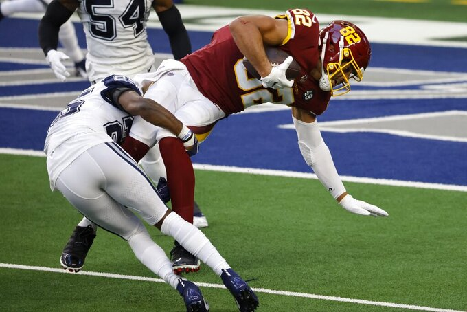 Dallas Cowboys safety Xavier Woods (25) stops Washington Football Team tight end Logan Thomas (82) from gaining more yardage after a catch in the first half of an NFL football game in Arlington, Texas, Thursday, Nov. 26, 2020. (AP Photo/Ron Jenkins)