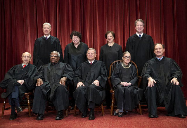 FILE - In this Nov. 30, 2018, file photo, the justices of the U.S. Supreme Court gather for a formal group portrait to include the new Associate Justice, top row, far right, at the Supreme Court building in Washington. Seated from left: Associate Justice Stephen Breyer, Associate Justice Clarence Thomas, Chief Justice of the United States John G. Roberts, Associate Justice Ruth Bader Ginsburg and Associate Justice Samuel Alito Jr. Standing behind from left: Associate Justice Neil Gorsuch, Associate Justice Sonia Sotomayor, Associate Justice Elena Kagan and Associate Justice Brett M. Kavanaugh. On Monday, May 4, 2020, the Supreme Court for the first time audio of court's arguments will be heard live by the world and the first arguments by telephone. (AP Photo/J. Scott Applewhite, File)