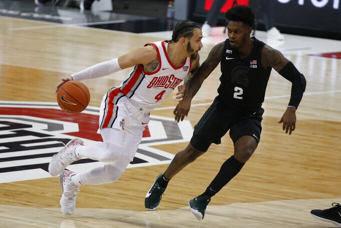 Ohio State's Duane Washington, left, brings the ball up court as Michigan State's Rocket Watts defends during the first half of an NCAA college basketball game Sunday, Jan. 31, 2021, in Columbus, Ohio. (AP Photo/Jay LaPrete)