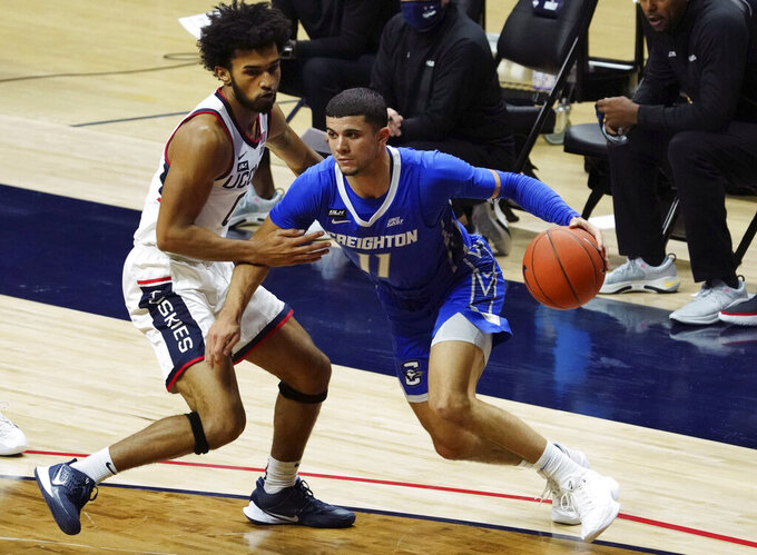 Creighton guard Marcus Zegarowski (11) drives the ball against Connecticut guard Jalen Gaffney (0) in the first half of an NCAA college basketball game in Storrs, Conn., Sunday, Dec. 20, 2020. (David Butler II/Pool Photo via AP)