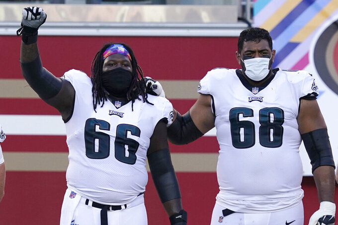 Philadelphia Eagles' Jamon Brown (66) raises his fist next to Jordan Mailata during the national anthem before an NFL football game against the San Francisco 49ers in Santa Clara, Calif., Sunday, Oct. 4, 2020. (AP Photo/Tony Avelar)