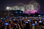 People use smartphones to film fireworks exploding at Tiananmen Square as part of a gala evening commemorating the 70th anniversary of the founding of Communist China light up the sky in Beijing, Tuesday, Oct. 1, 2019. China's Communist Party marked 70 years in power with a military parade Tuesday that showcased the country's global ambitions while police in Hong Kong fought protesters in a reminder of strains at home. (AP Photo/Andy Wong)