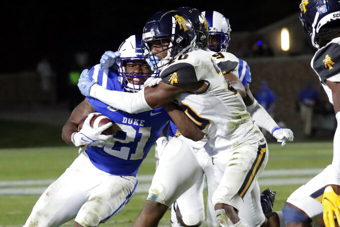 Duke running back Mataeo Durant (21) takes a hit from North Carolina A&T defensive back Najee Reams (20) during the second half of an NCAA college football game in Durham, N.C., Friday, Sept. 10, 2021. (AP Photo/Chris Seward)