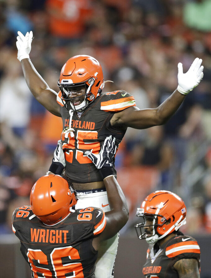 Cleveland Browns running back Dontrell Hilliard (25) celebrates with Willie Wright (66) after Hilliard scored a 7-yard touchdown during the first half of the team's NFL preseason football game against the Detroit Lions, Thursday, Aug. 29, 2019, in Cleveland. (AP Photo/Ron Schwane)