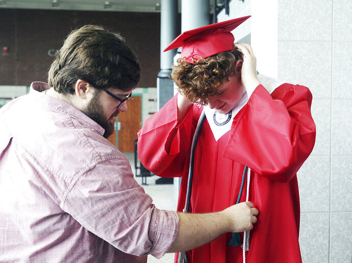 In this May 19, 2019 photo, Phill Luallen, of Louisville, left, helps his younger brother Nate Heady straighten his tassels during the Owensboro Innovation Academy at the RiverPark Center in Owensboro, Ky. Kentucky Commissioner of Education Wayne Lewis told the first graduating class of the Owensboro Innovation Academy that he was proud to stand before the 59 students who blazed the trail to become the first New Tech high school in Kentucky.  (Bobbie Hayse/The Messenger-Inquirer via AP)