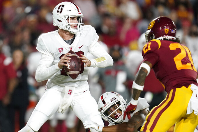Stanford quarterback Tanner McKee, left, scrambles out of the pocket during the first half of the team's NCAA college football game against Southern California on Saturday, Sept. 11, 2021, in Los Angeles. (AP Photo/Marcio Jose Sanchez)