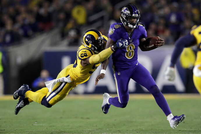 Baltimore Ravens quarterback Lamar Jackson, right, is tackled by Los Angeles Rams defensive end Dante Fowler during the second half of an NFL football game Monday, Nov. 25, 2019, in Los Angeles. (AP Photo/Marcio Jose Sanchez)