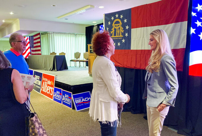 Former Sen. Kelly Loeffler, R-Ga., greets GOP activists Saturday, April 16, 2021, ahead of the Fulton County Republican Party convention in Alpharetta, Ga. Loeffler lost her Jan. 5 Senate runoff in part because some conservatives considered her insufficiently supportive of former President Donald Trump and his false claims that the 2020 election was rigged. Loeffler, who is considering another Senate bid in 2022, told her home county Republicans that she visited Trump's Florida resort recently. She urged party unity and warned that anything else will end with Republicans losing Georgia again next year. (AP Photo/Bill Barrow)