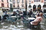 Tourists and residents resume their normal routine at a bar in Venice, Italy, Sunday, Nov. 17, 2019. High tidal waters returned to Venice on Sunday, days after the city experienced its worst flooding in more than 50 years. Venetians coped with another exceptional tide Sunday in a season that is setting records while other parts of Italy wrestled with a cornucopia of weather woes, from rain-swollen rivers to high winds to an out-of-season avalanche. (Emiliano Creeps/ANSA via AP)