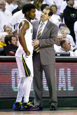 Baylor head coach Scott Drew, right, talks with guard Davion Mitchell, left, near the bench during the second half of an NCAA college basketball game against Kansas on Saturday, Feb. 22, 2020, in Waco, Texas. (AP Photo/Ray Carlin)