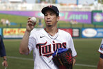Minnesota Twins starting pitcher Kenta Maeda tosses a ball to a fan before pitching against the Boston Red Sox in a spring training baseball game Monday, Feb. 24, 2020, in Fort Myers, Fla. (AP Photo/John Bazemore)