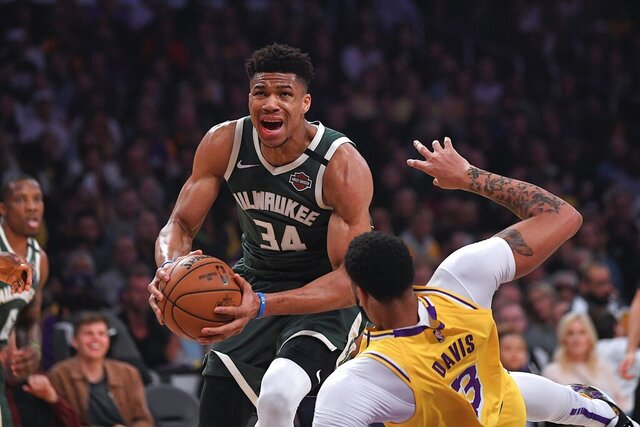 FILE - In this March 6, 2020, file photo, Milwaukee Bucks forward Giannis Antetokounmpo knocks down Los Angeles Lakers forward Anthony Davis as he drives to the basket during the first half of an NBA basketball game in Los Angeles. Jusuf Nurkic is back and healthy. So are Zach Collins, Meyers Leonard, Giannis Antetokounmpo, Anthony Davis and plenty of others. If the four-month NBA shutdown had a silver lining, it's that a lot of ailing players got well. (AP Photo/Mark J. Terrill, File)